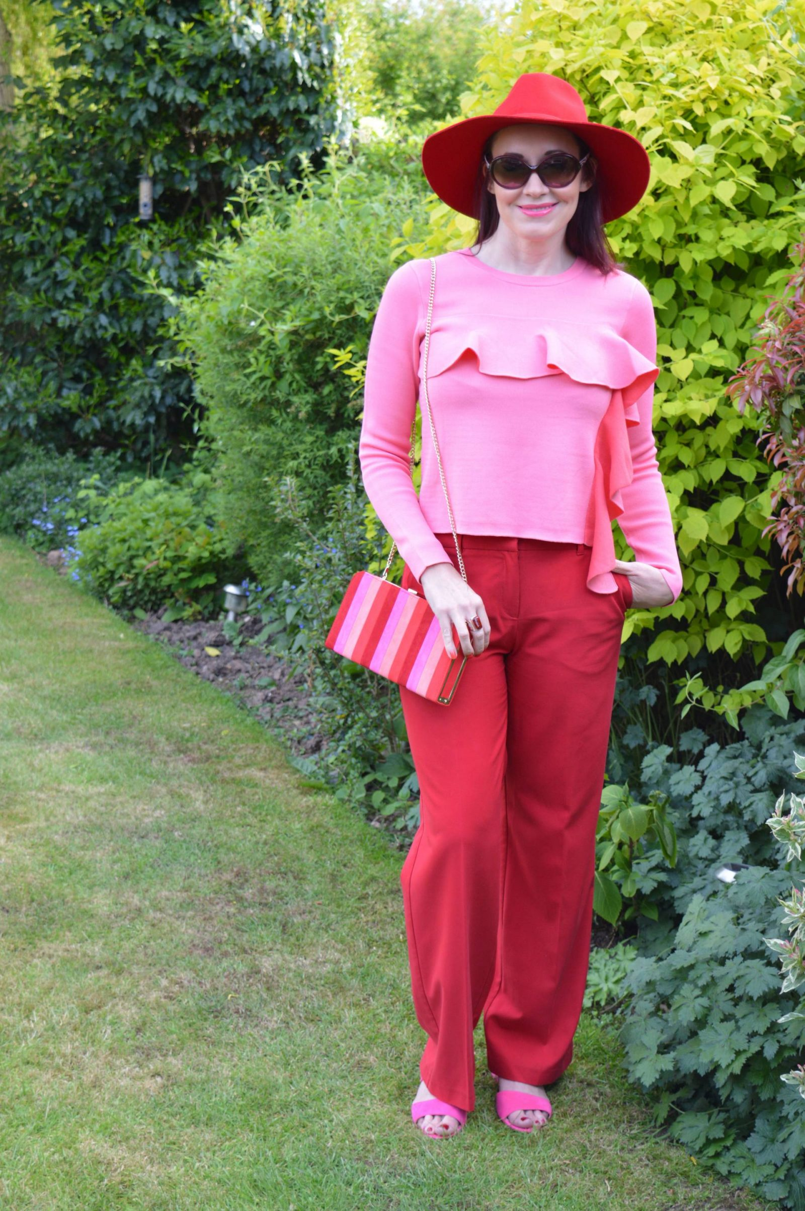 Colour blocking red and pink with Lotus shoes and Sheraton clutch bag Asos pink ruffle jumper