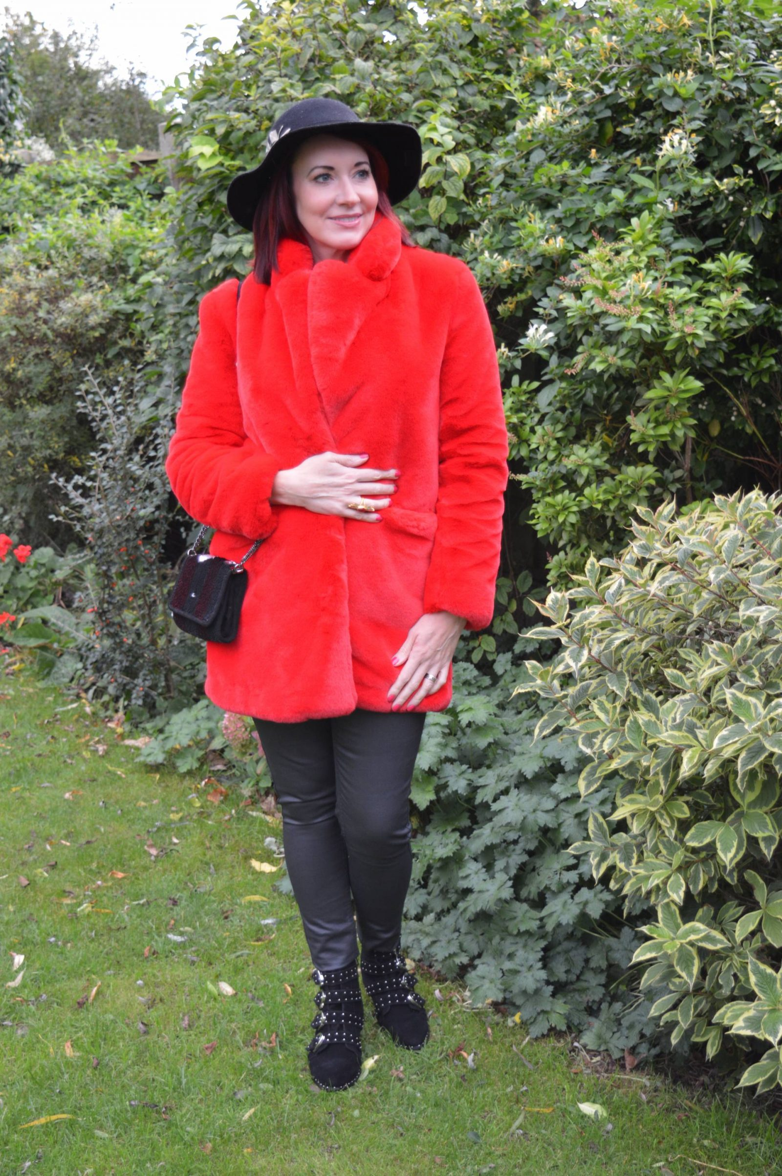 Red faux fur coat and black coated jeans