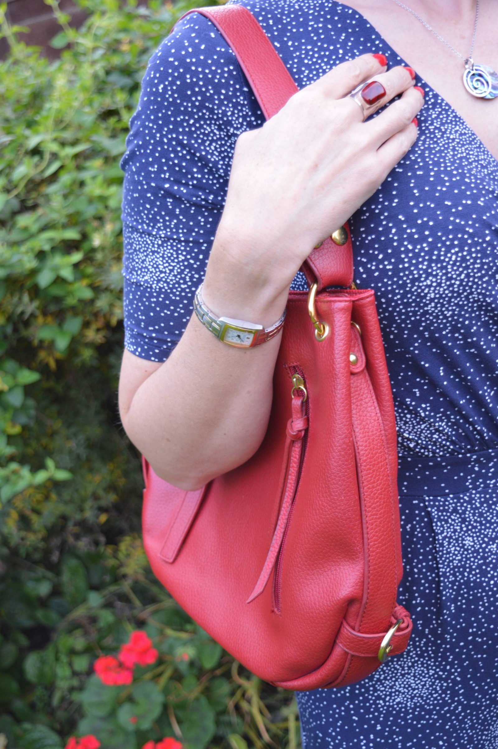 Styling a jumpsuit for day to night Laura Ashley navy jumpsuit red leather shoulder bag