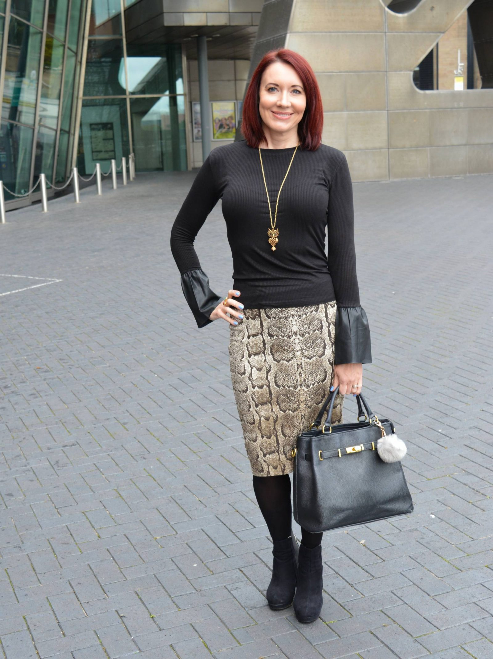 Snake print pencil skirt, black top with faux leather statement sleeves, Mila Blu black bag, Pia long owl necklace