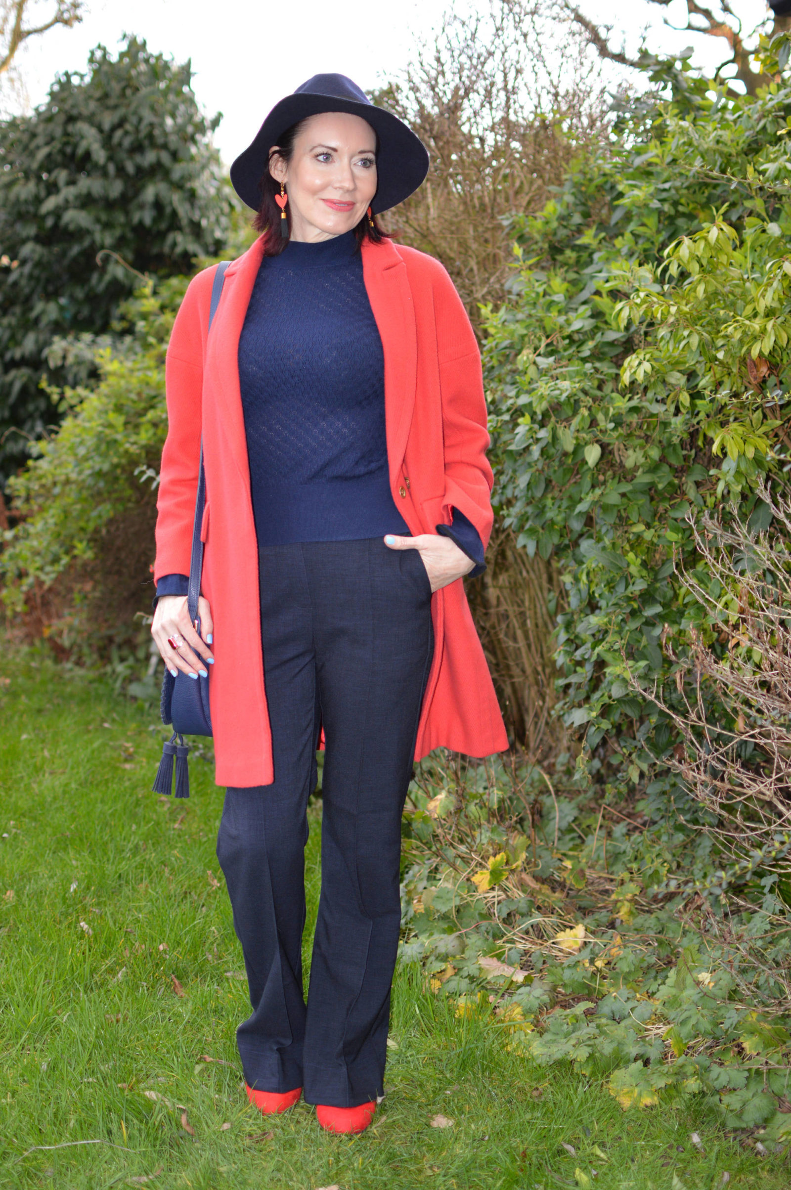 Classic navy trousers and sweater with a red coat