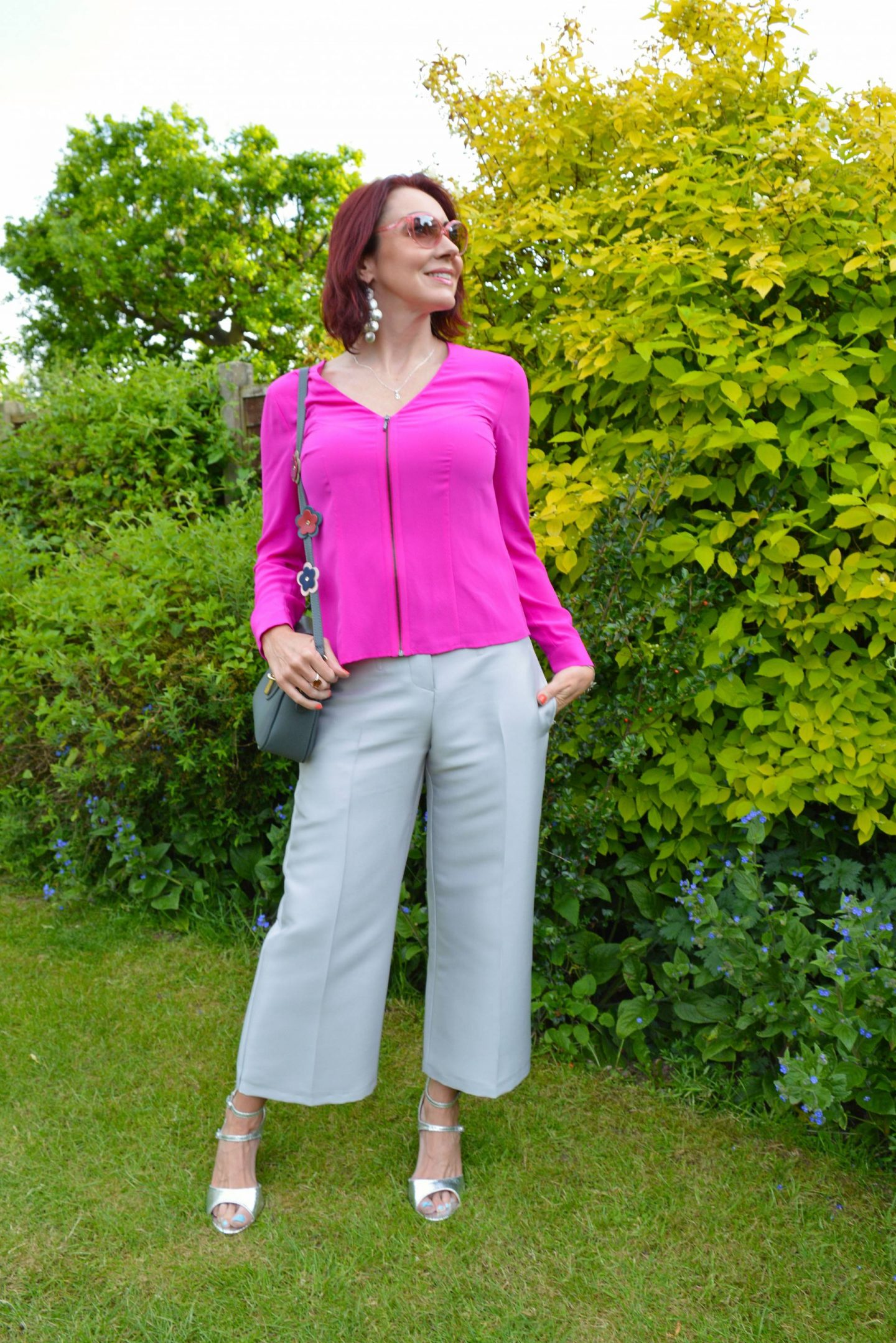 Outline silver cropped trousers and hot pink blouse