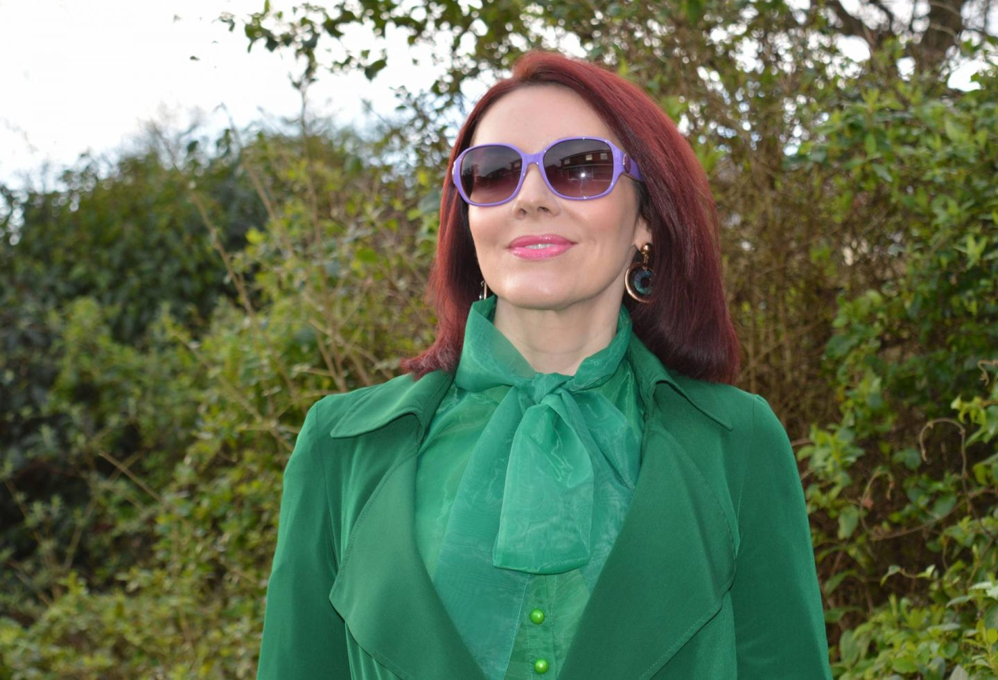 emerald green Papaya trenchcoat, green organza bow blouse, purple Ted Baker sunglasses
