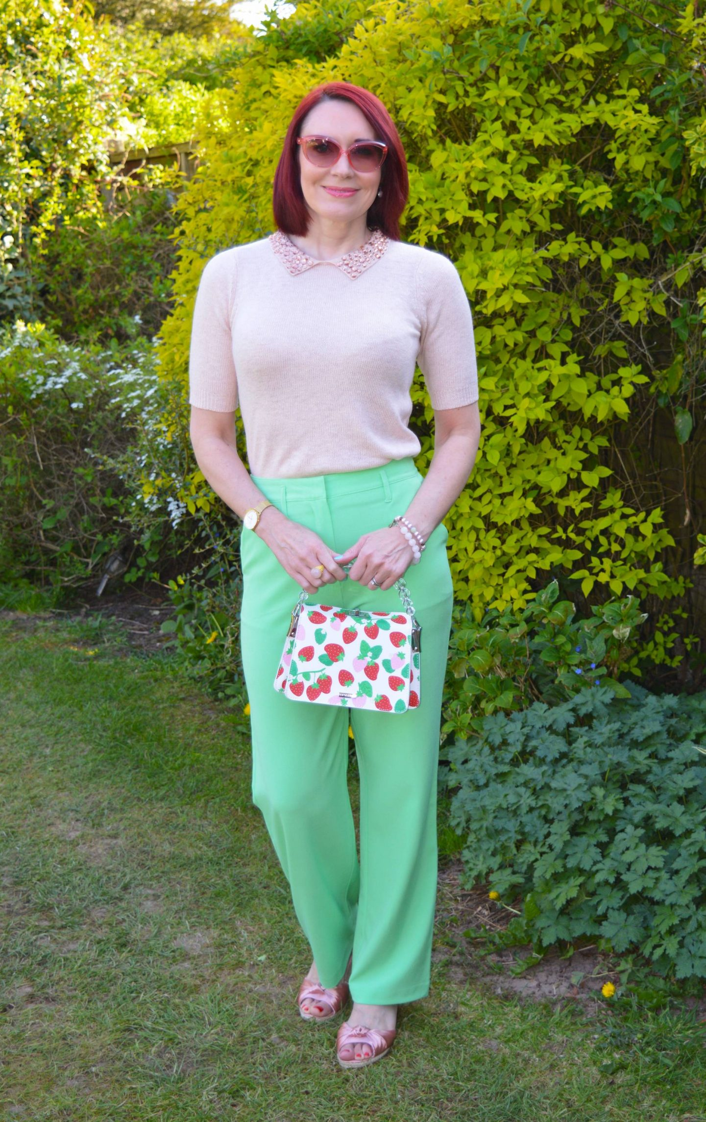 Wearing Our Spring Sweaters, blush pink short sleeve sweater, lime green trousers, Skinny Dip strawberry print bag