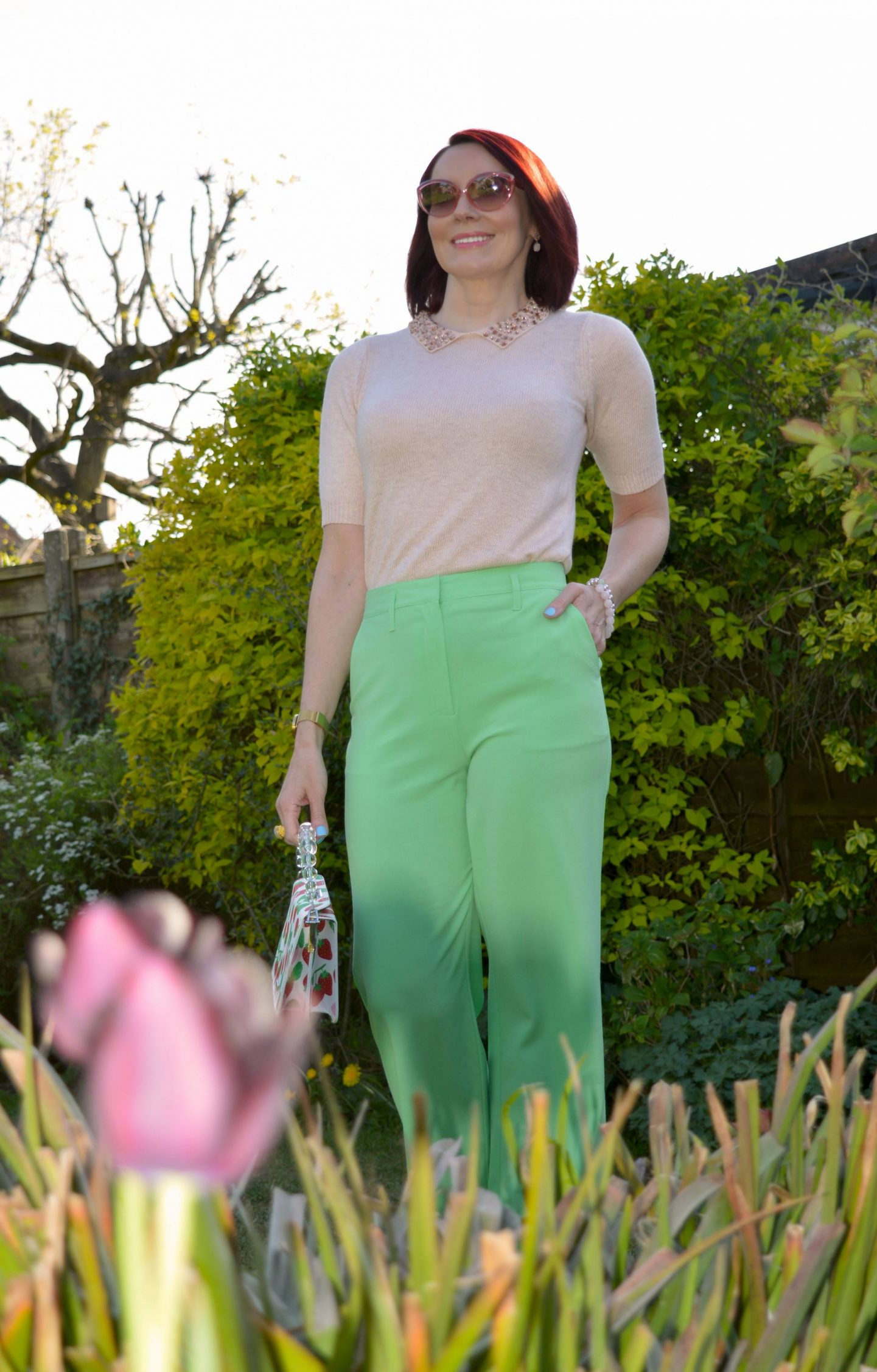 Wearing Our Spring Sweaters, blush pink short sleeve sweater, lime green trousers, Skinny Dip strawberry print bag, Coast pink satin wedge sandals