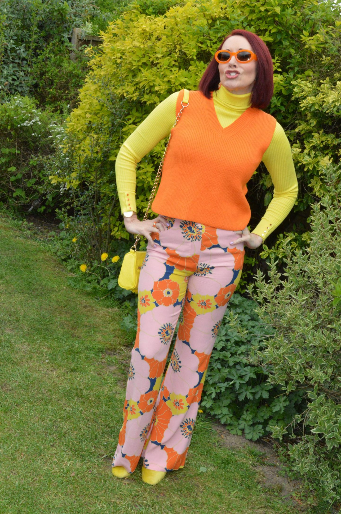 Zara floral print trousers and orange knitted vest