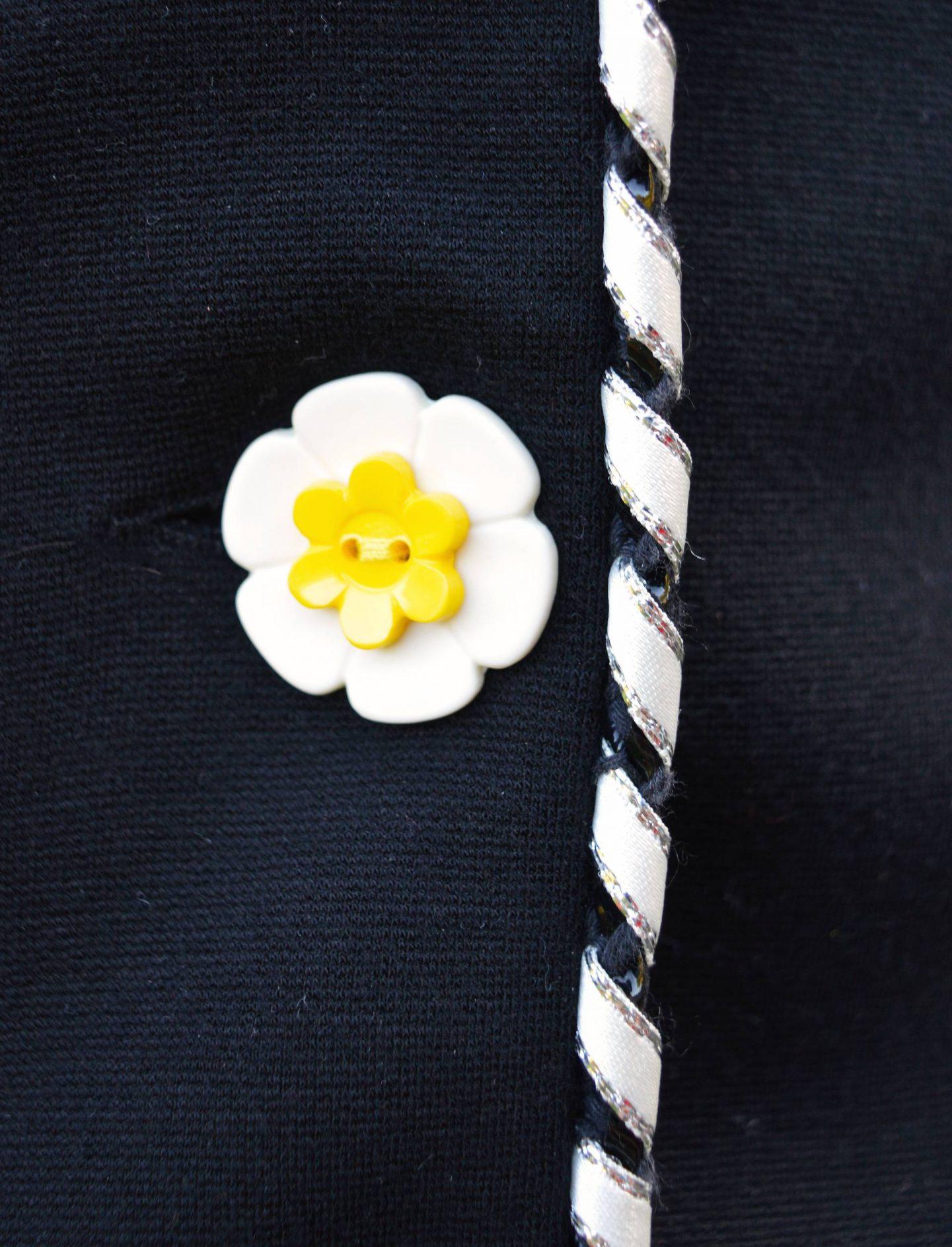 close up of flower button on a black Marks & Spencer jacket