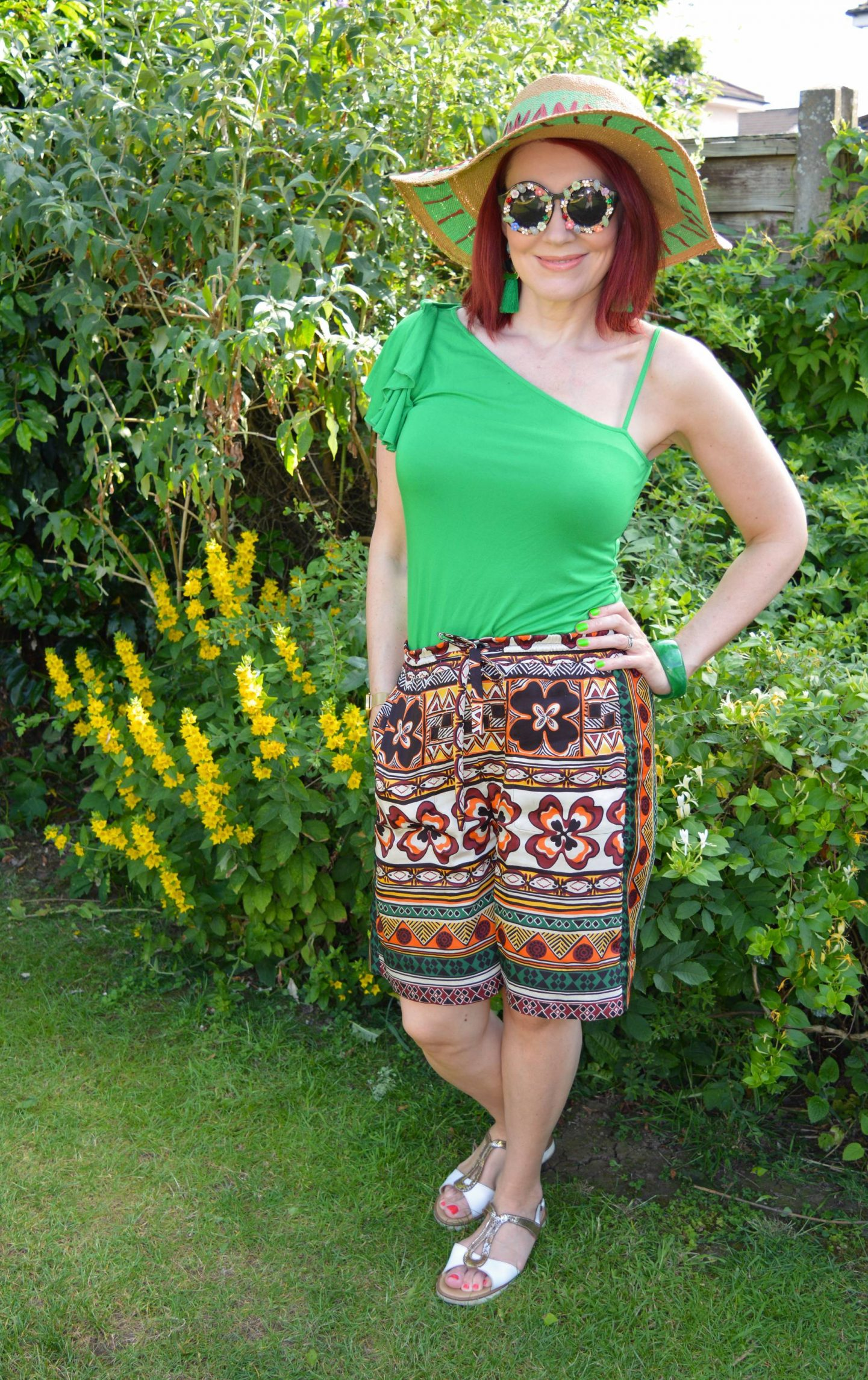 Karen Millen green one shoulder top, Zara print bermuda shorts, Oliver Bonas  wanderlust hat, Katy Perry embellished sunglasses