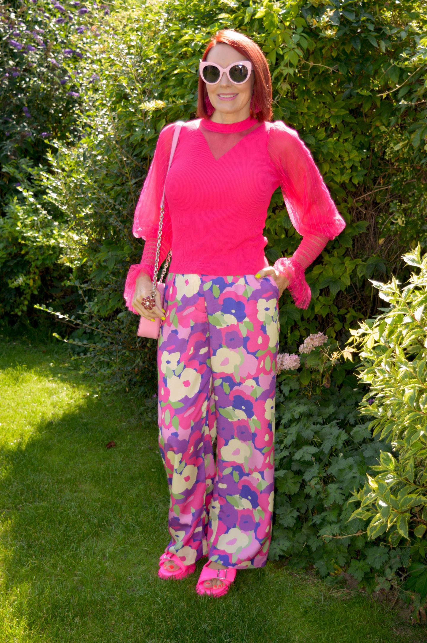 Styling Our Statement Sleeves - August's Style Not Age, River Island pink sheer sleeve top, Monki purple print trousers, RIver Island pink cat eye sunglasses, Asos pink sporty mules, Nali pink camera bag