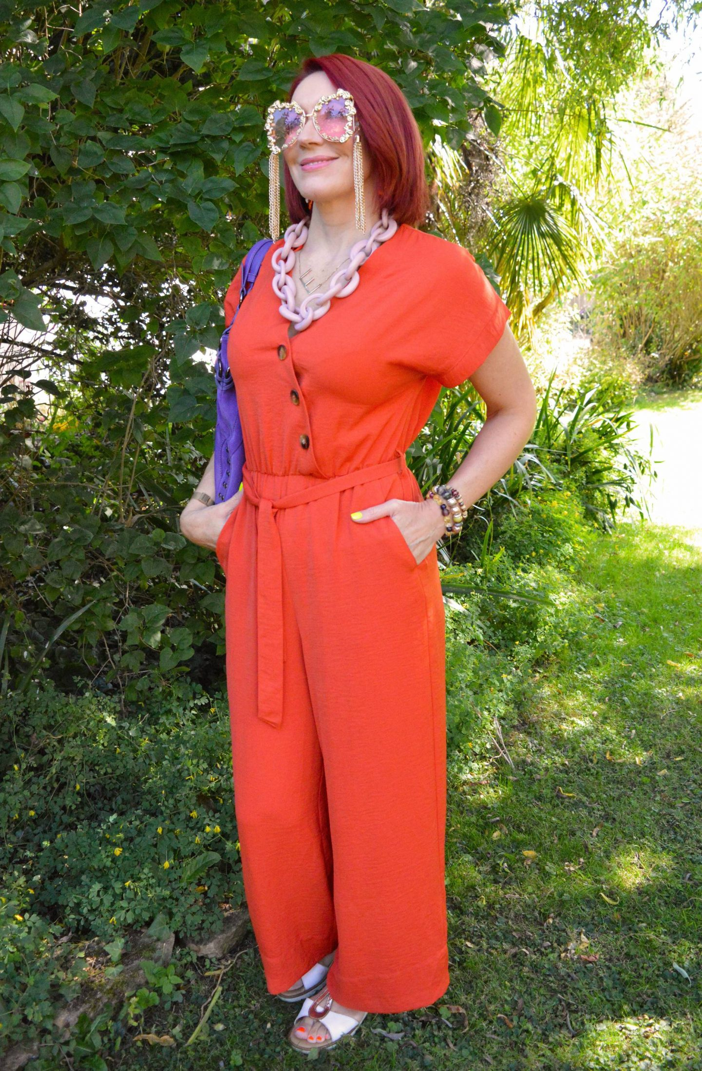 Orange Belted Jumpsuit, Ri2k purple bag, Meghan Fabulous gold sunglasses